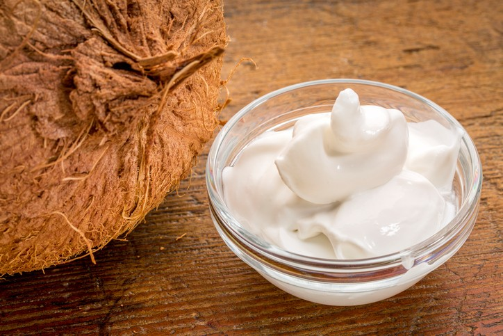 coconut milk yogurt - a small glass bowl against rustic wood with a coconut